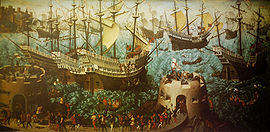 A small fleet of large, highly decorated carracks are riding on a wavy sea. In the foreground are two low, fortified towers bristling with cannon and armed soldiers and retinue walking between them.